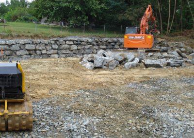 Erdbau Steinschlichtung Bagger umgeben von Steinen vor Steinwand