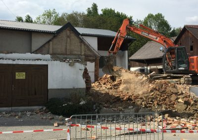 Erdbau Abbruch Bagger auf Hausresten vor demolierter Wand